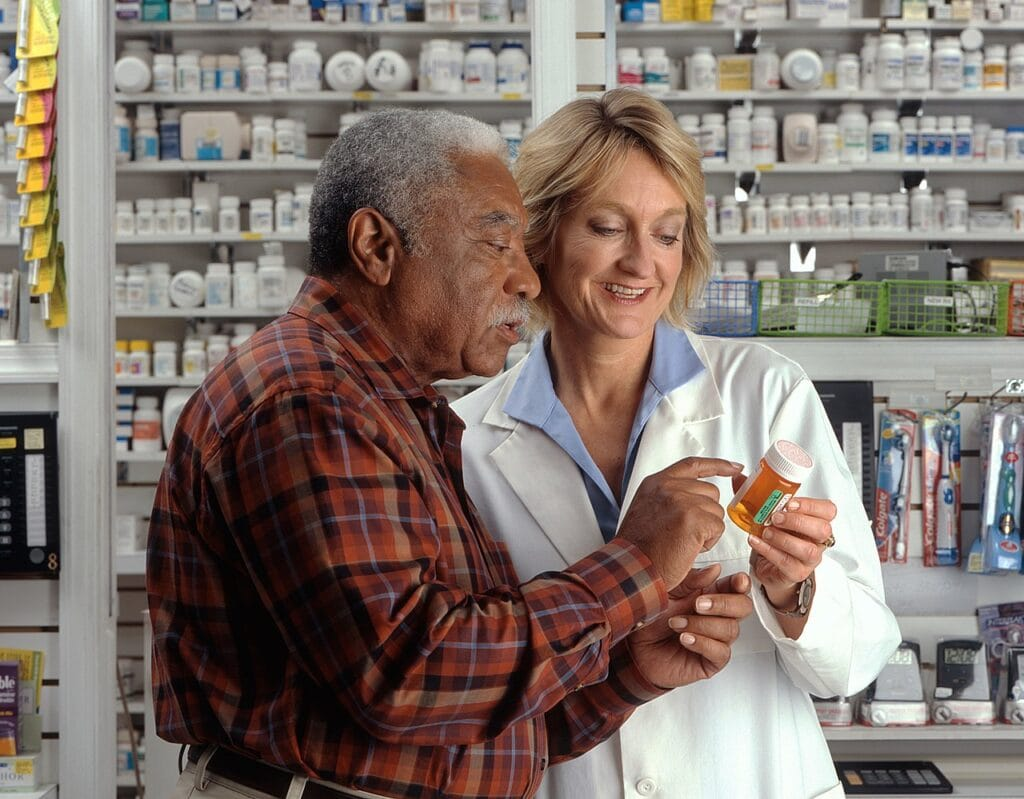 Man consults with pharmacist https://commons.wikimedia.org/wiki/File:Man_consults_with_pharmacist.jpg